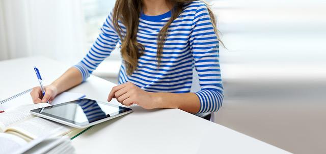 Student sitzt am Schreibtisch und liest am Tablet