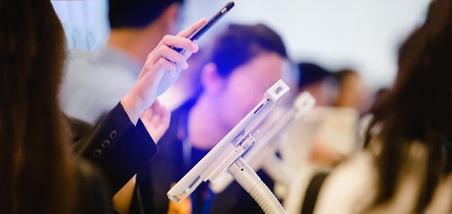 Hand hält Smartphone und scannt QR-Code über Tablet für die Registrierung